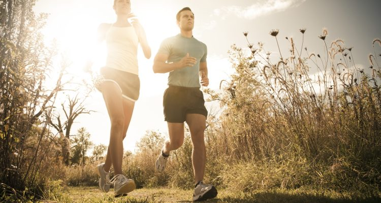 Caucasian couple running together on path